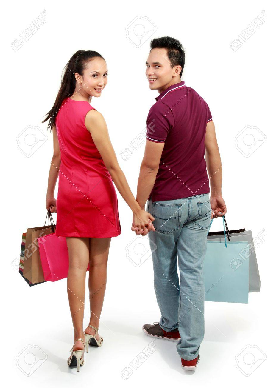 full lenght portrait of happy couple walking with shopping bag on white background Stock Photo - 13528194