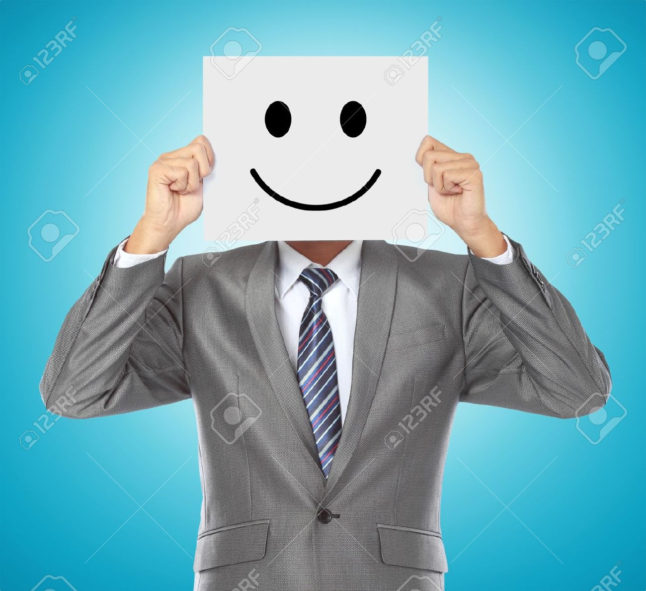 businessman covering his face with smiling mask on blue background Stock Photo - 14619480