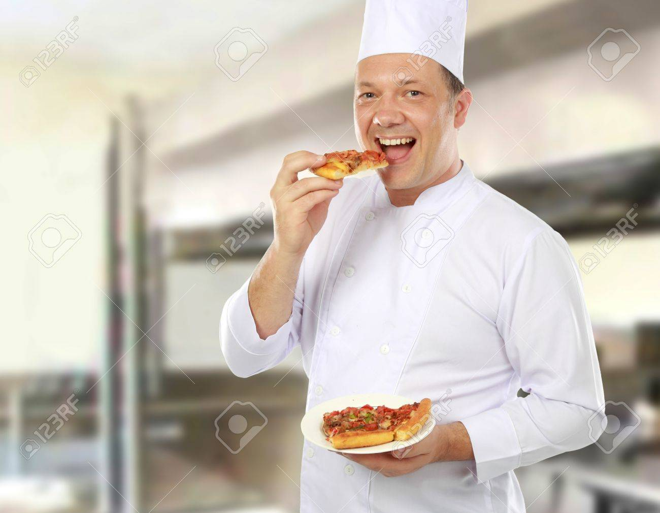 Chef Eating And Taste A Pizza Of His In The Kitchen Stock Photo ...