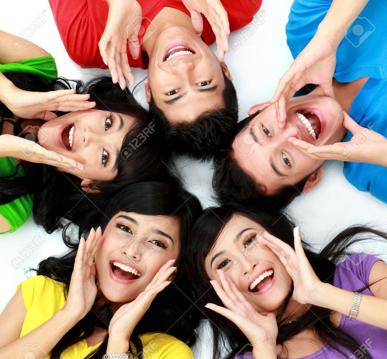 happy group of friends screaming with their heads together on the floor Stock Photo - 16035501