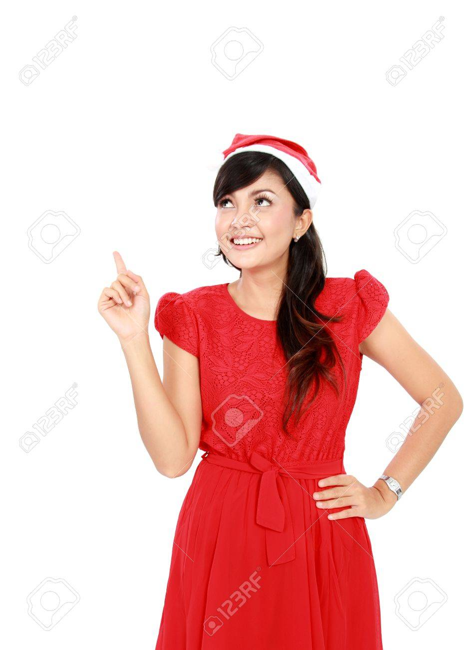 Woman with santa hat in red dress pointing up - isolated on white background. Stock Photo - 16800546