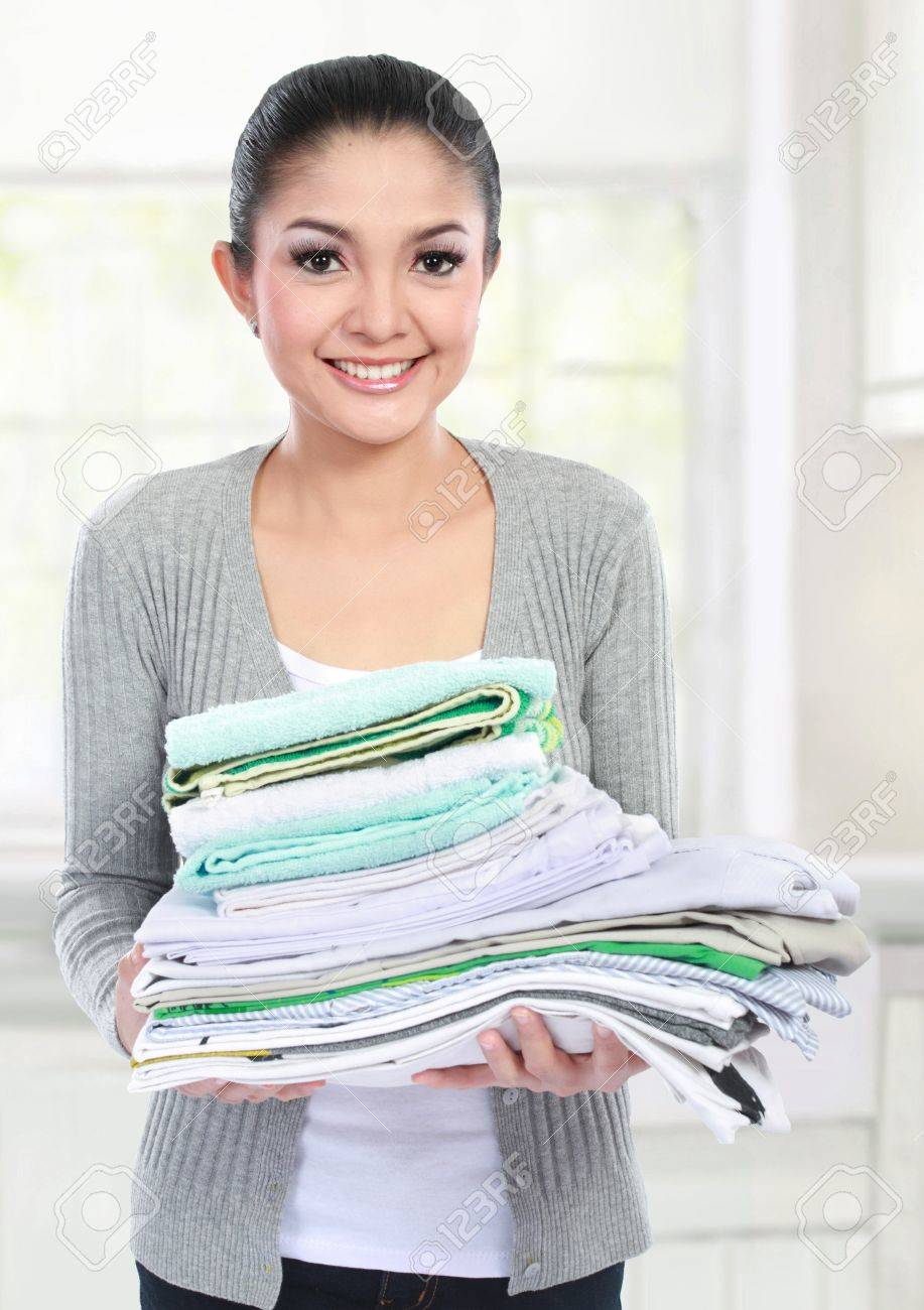 smiling woman doing a housework holding stack of clean clothes Stock Photo - 18892578