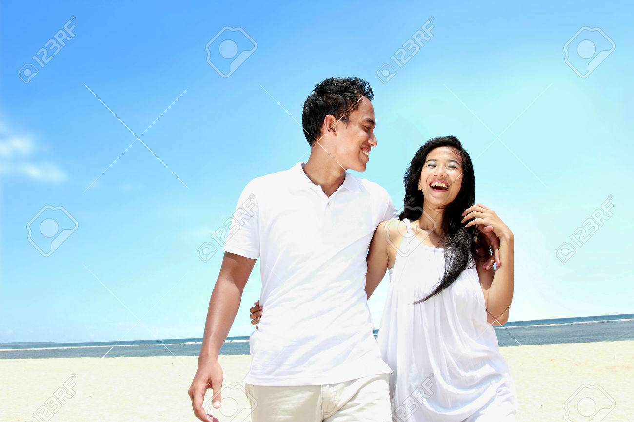 Portrait of beach couple in white dress having fun laughing together Stock Photo - 24658387