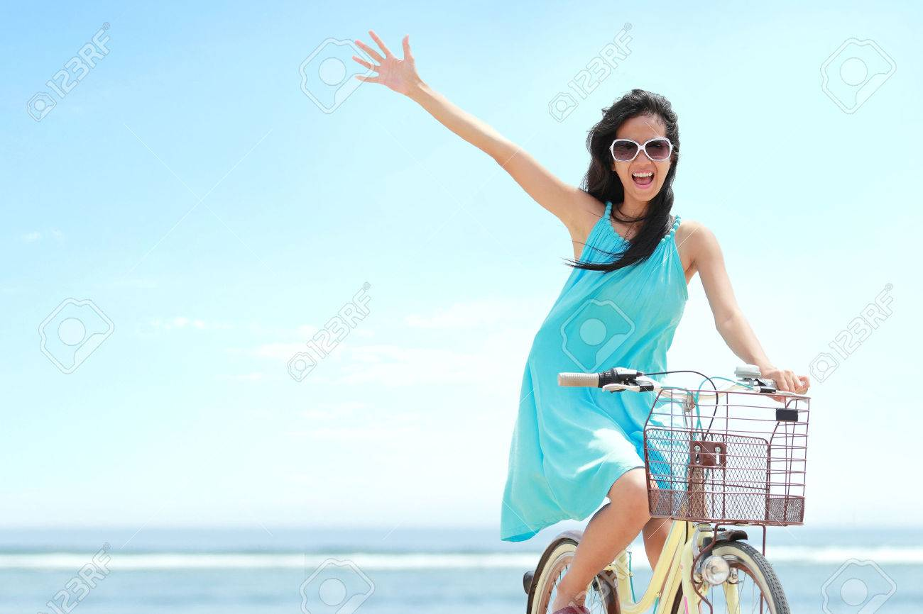 carefree woman having fun and smiling riding bicycle at the beach Stock Photo - 27775406
