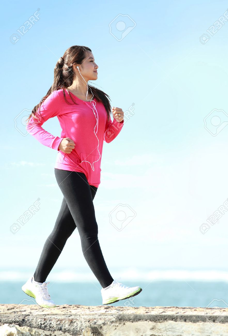 Happy healthy girl doing a brisk walking on the beach - 29822227