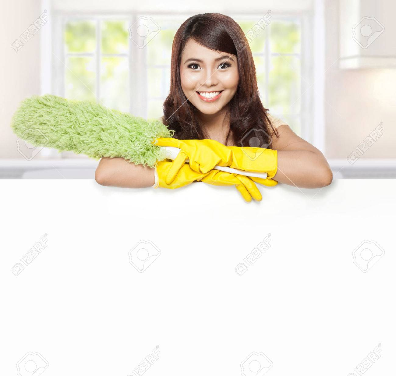 White gloves apron cleaning services - Cleaning Service Woman Presenting A Blank Board And Hold A Duster Stock Photo 34711729