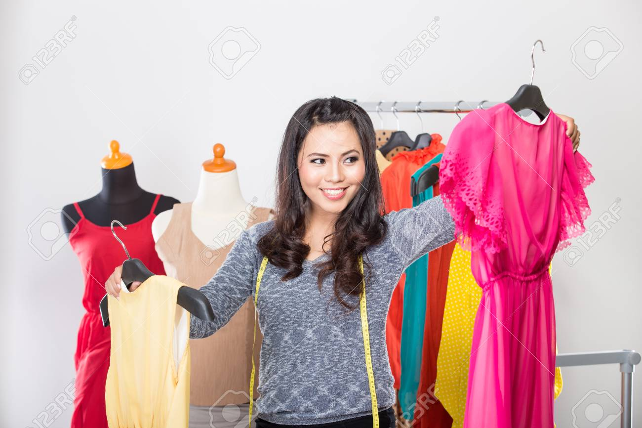 Asian Designer Clothes | A Portrait Of A Young Asian Designer Comparing Two Dresses In