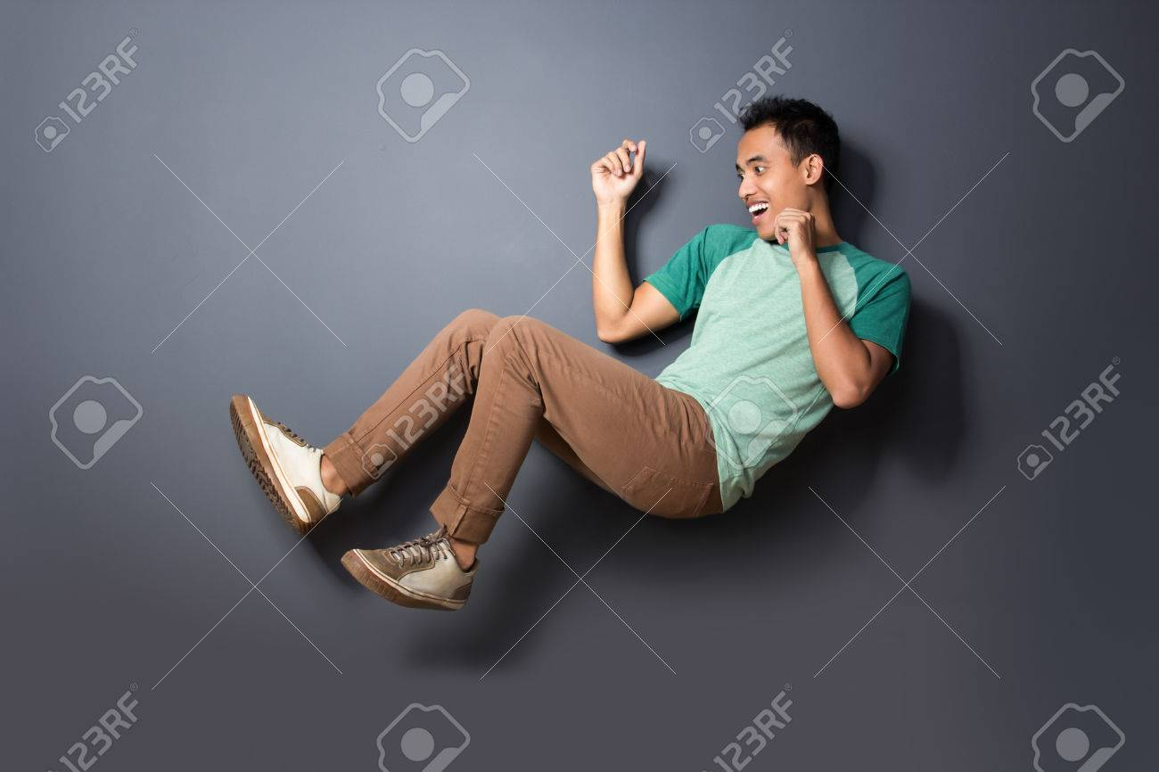 Portrait Of Young Man Floating And Act Like Fall Over Isolated On Dark Background Stock Photo