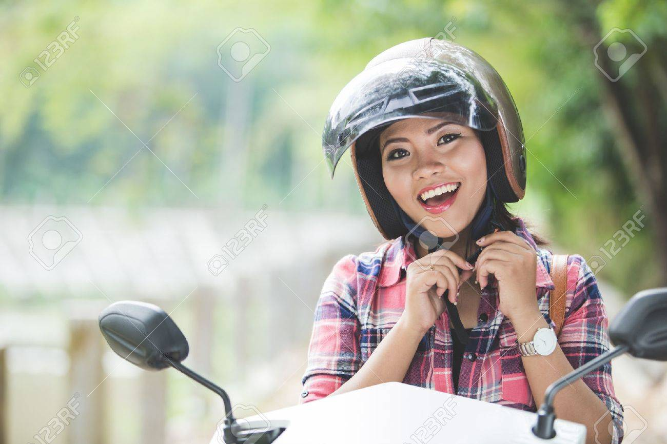 A portrait of a young asian woman wearing a helmet before riding a motorcycle on a park Stock Photo - 50512337