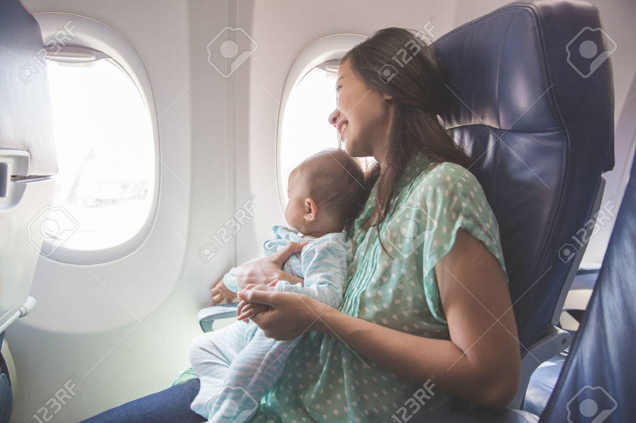 Happy mother and baby sitting together in airplane cabin near window - 50512395