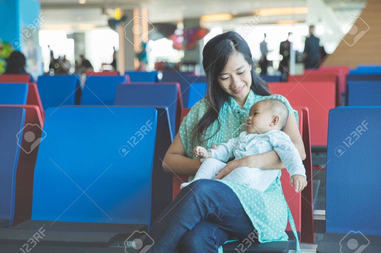 portrait of cute little baby waiting in the airport with her mother Stock Photo - 50512749