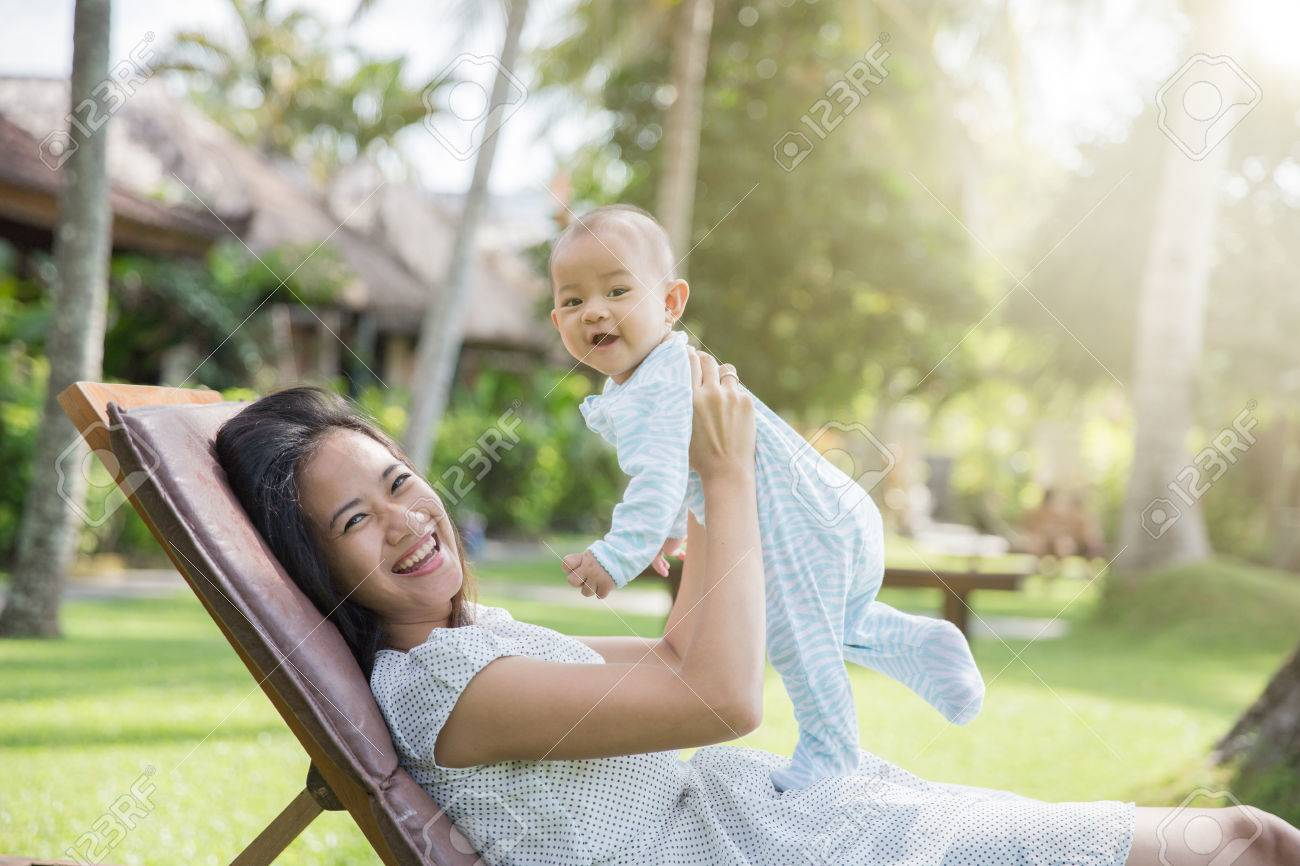 portrait of a beautiful asian mother having fun with his baby on a sunny day Stock Photo - 50862442