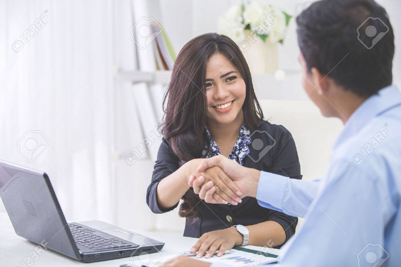 Pretty asian business woman shaking hands with businessman in her office during meeting - 53376189