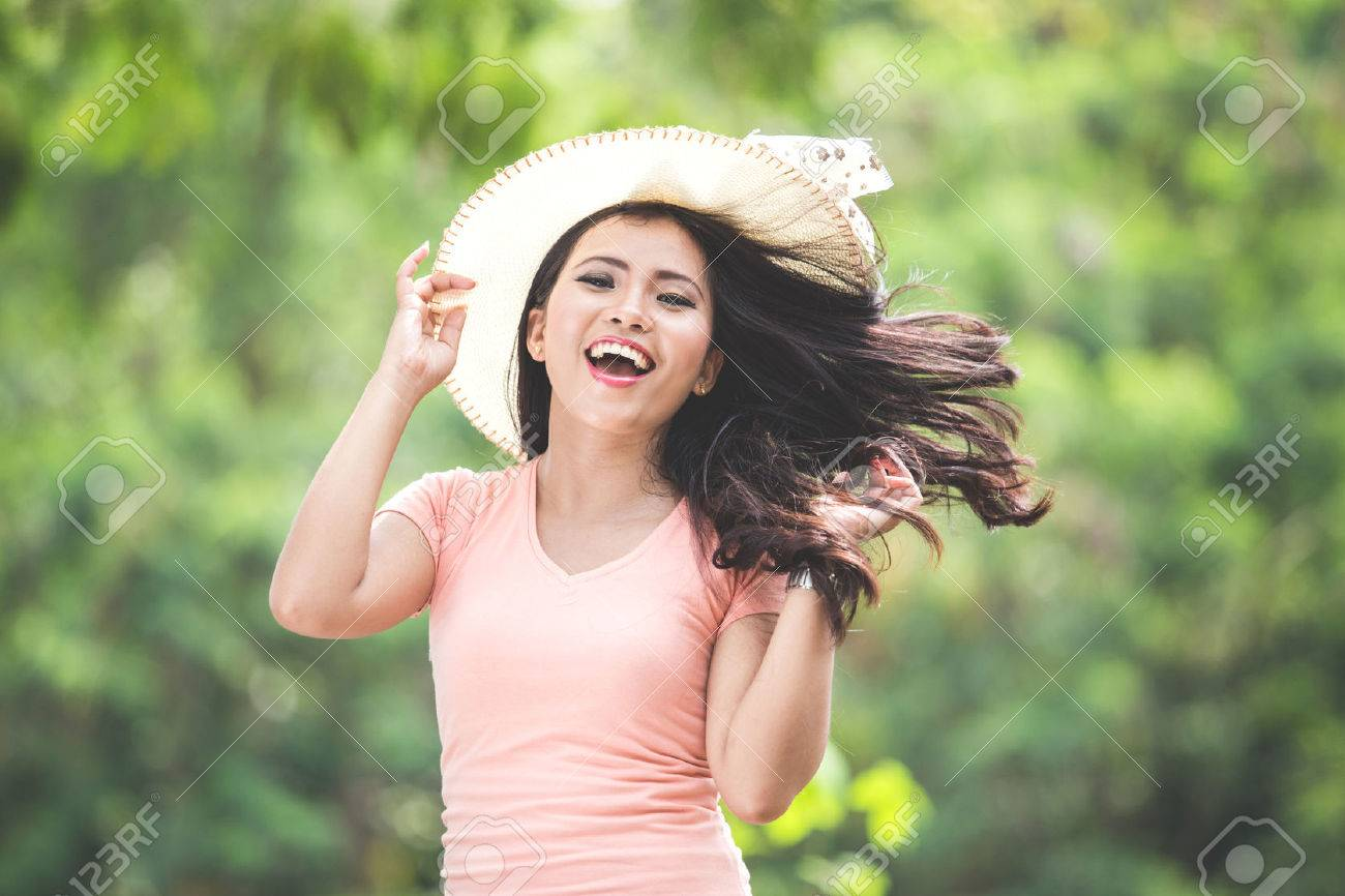 A portrait of a beautiful young asian woman wearing round hat on a park Stock Photo - 52178920