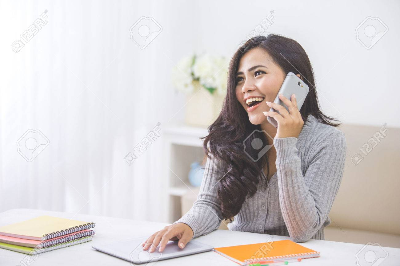portrait of casual asian woman making a phone call at home using smart phone - 53376192