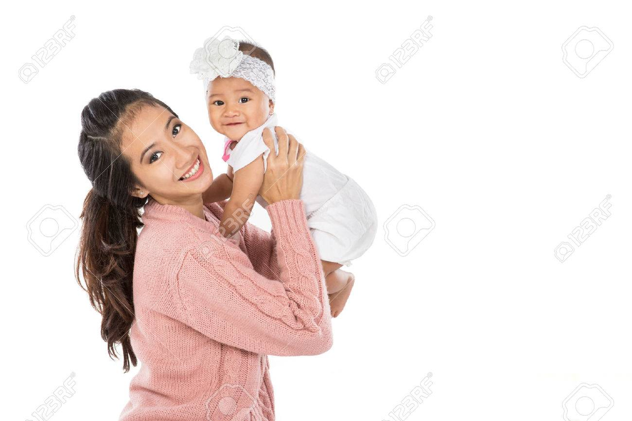 Asian woman holding her baby girl isolated over white background - 53046124