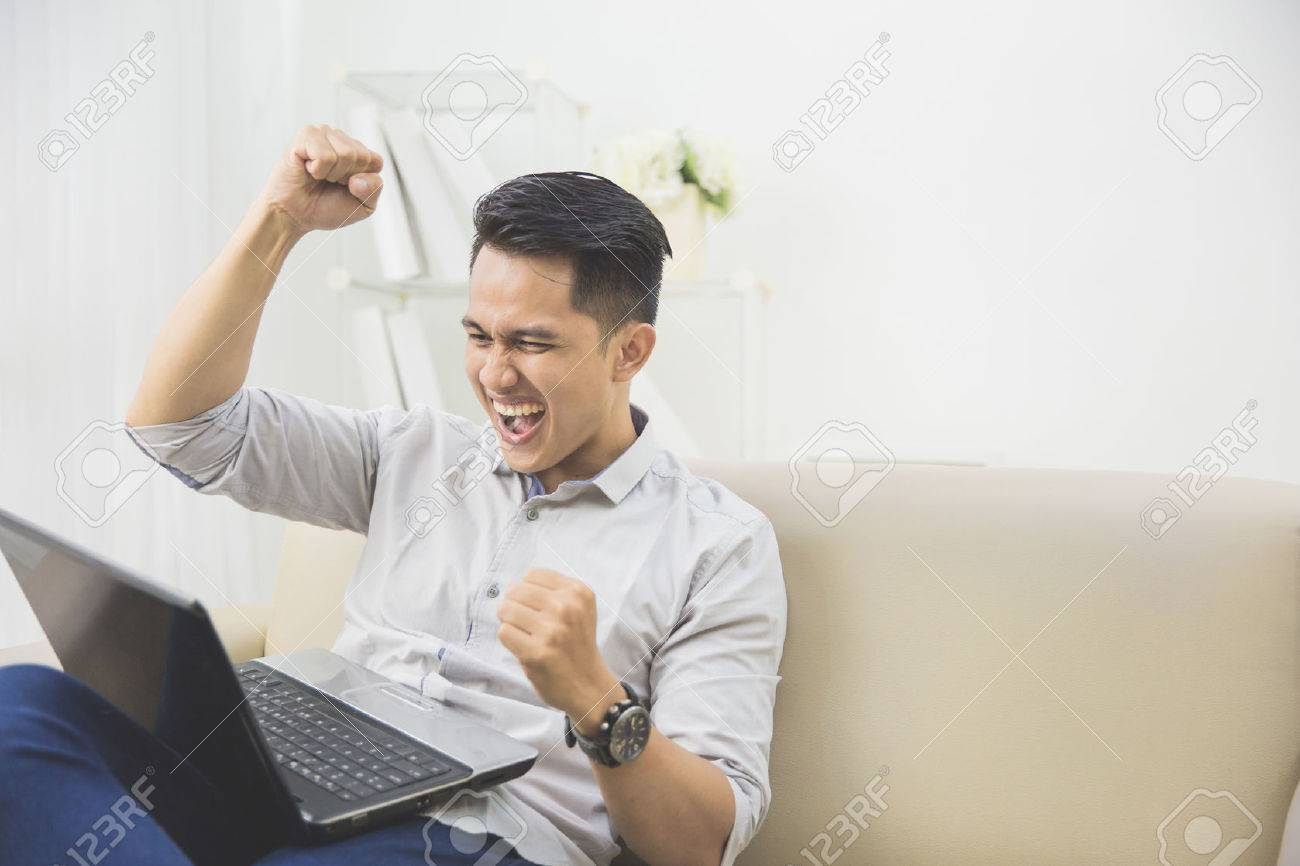 happy excited young man with laptop at home sitting on a couch Stock Photo - 53046899