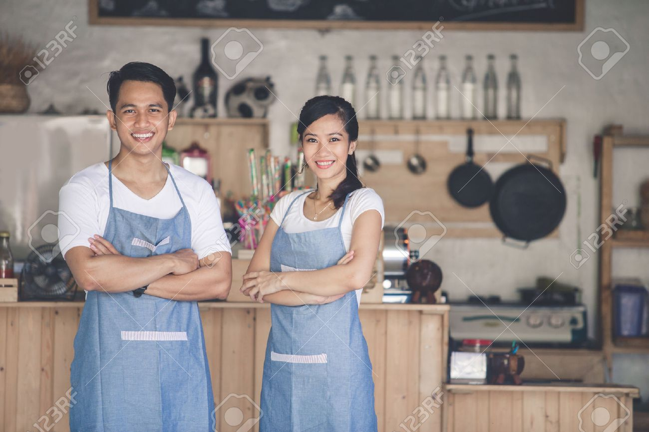 Successful small business owner proudly standing in front of their cafe - 54110556