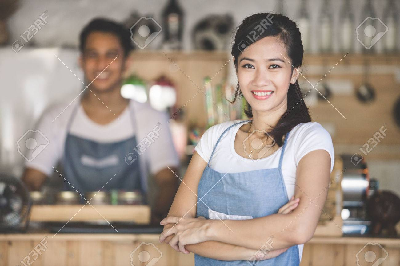 Successful small business owner standing with crossed arms with partner at the background Stock Photo - 54110804