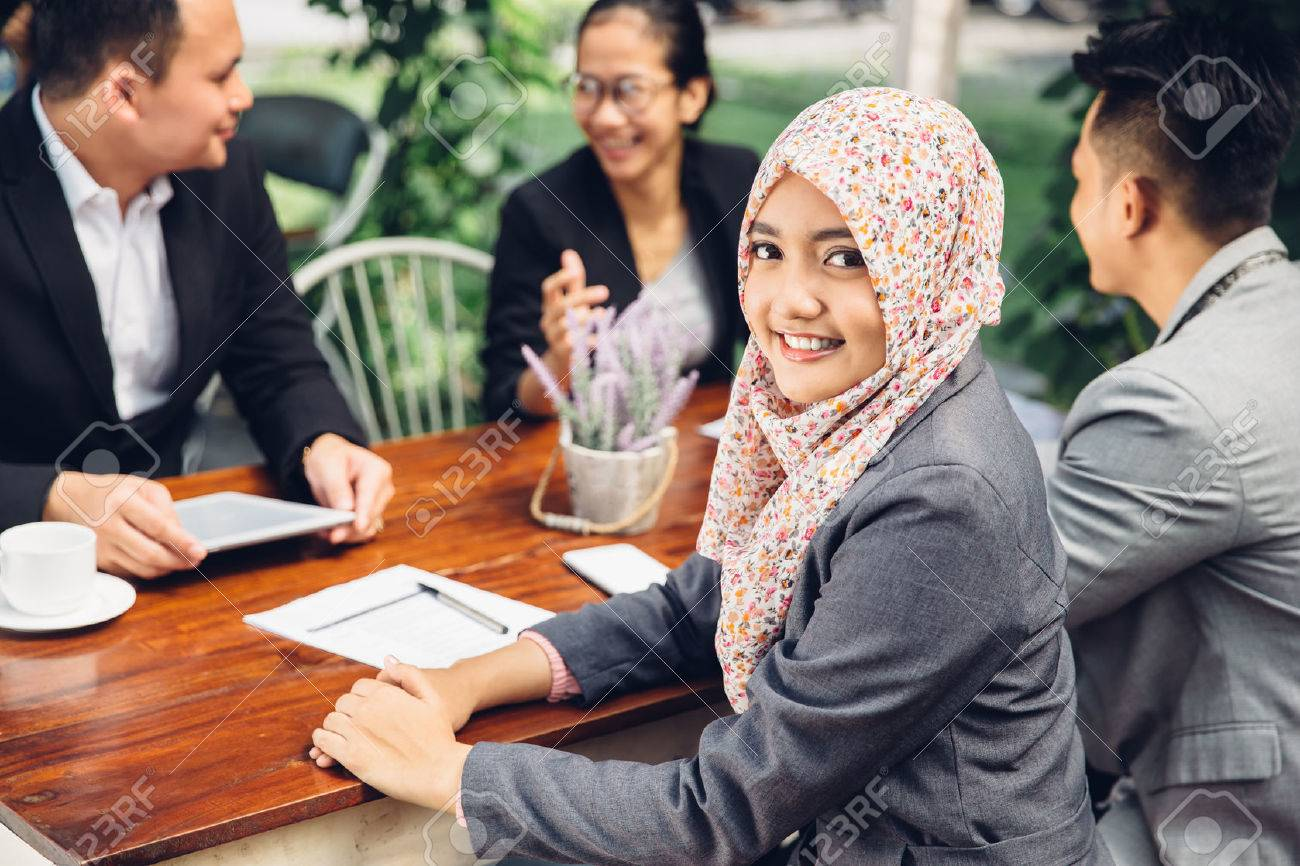 Attractive asian businesswoman smiling at the camera during a business meeting Stock Photo - 54677024