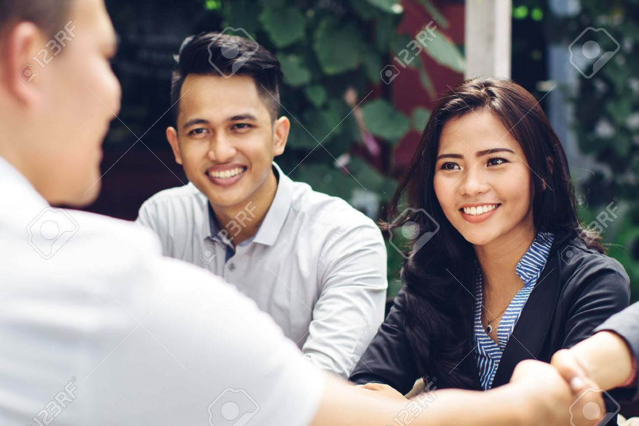 portrait of young asian business people meeting in a cafe and shake hand Stock Photo - 54702136