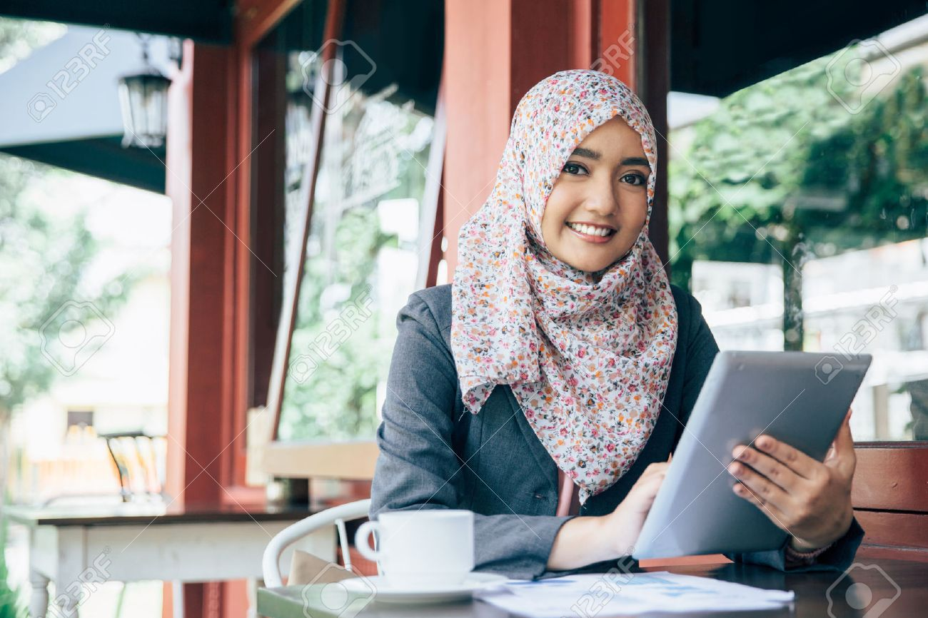 Young businesswoman on a coffee break. Using tablet computer Stock Photo - 54702712