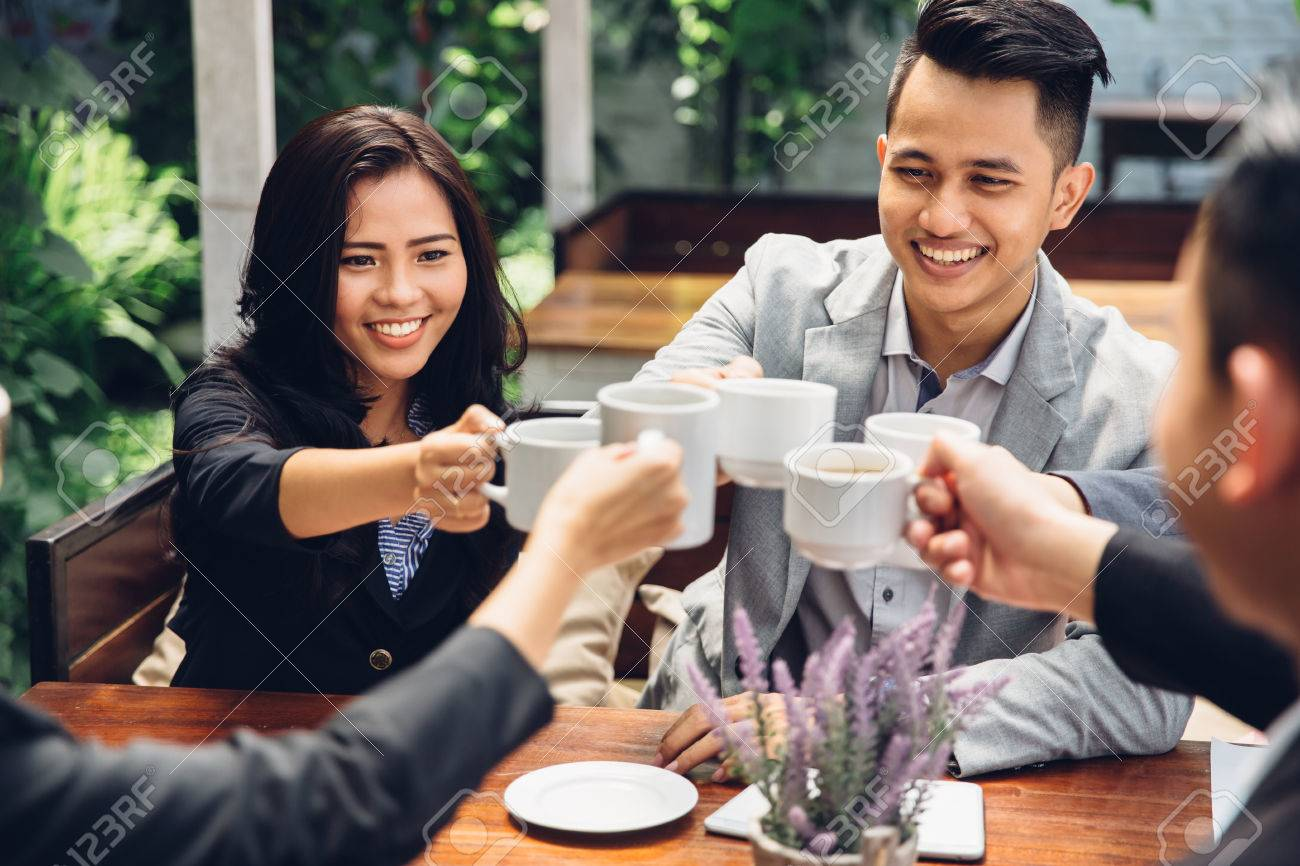 happy asian business Friends Cheering With Coffee at cafe Stock Photo - 54702714