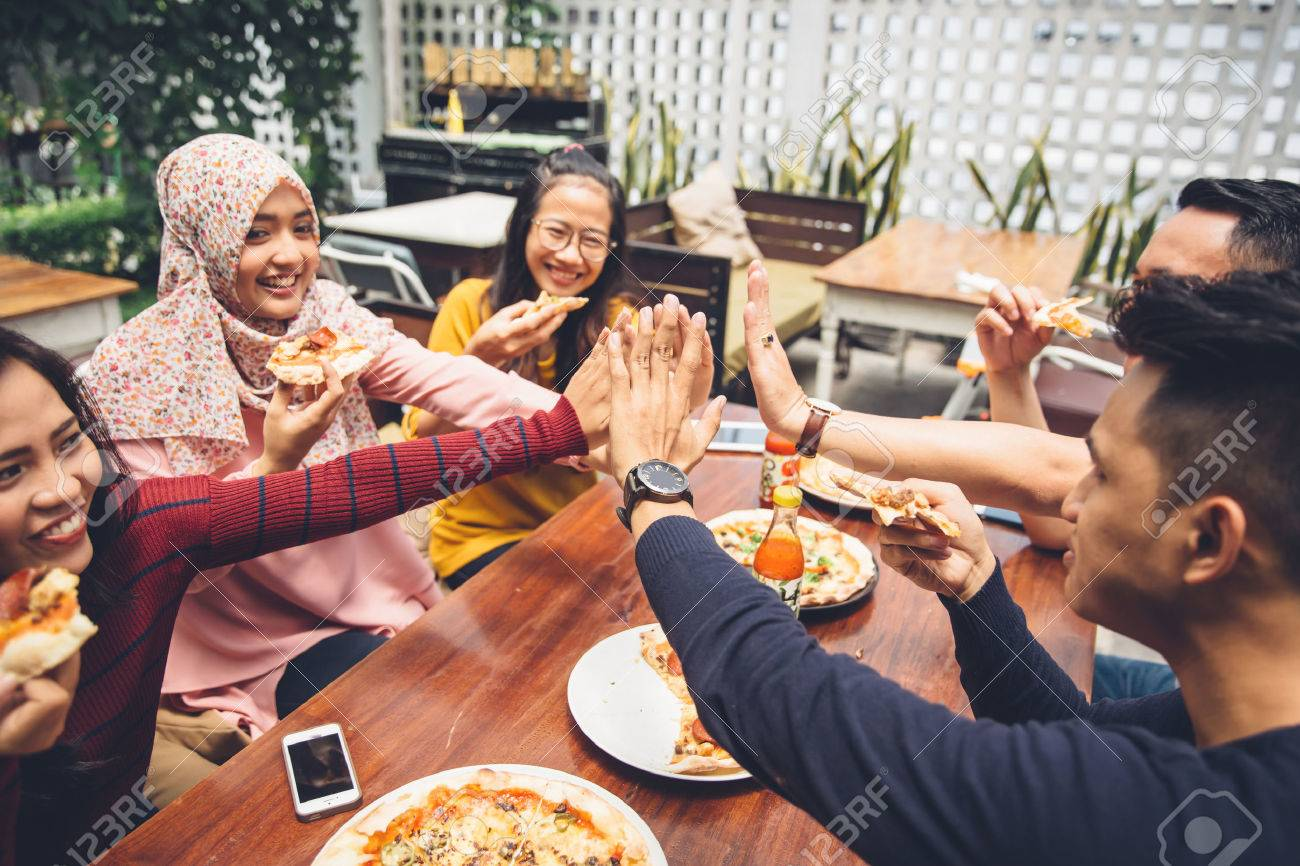 portrait of asian friend giving high five at cafe while having a lunch Stock Photo - 54705456