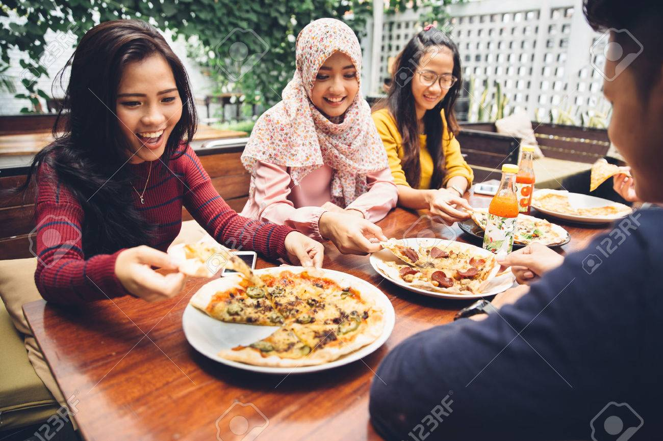 Group Of Young Friends Enjoying Meal In Outdoor Restaurant Stock Photo - 54706555