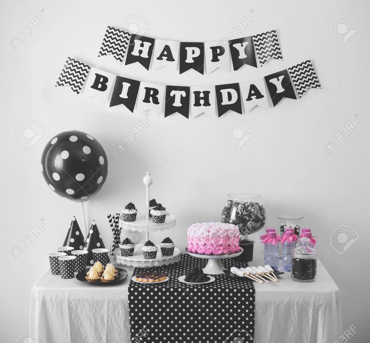 porträt schwarzweiß-geburtstags-party-dekoration mit voller kuchen
