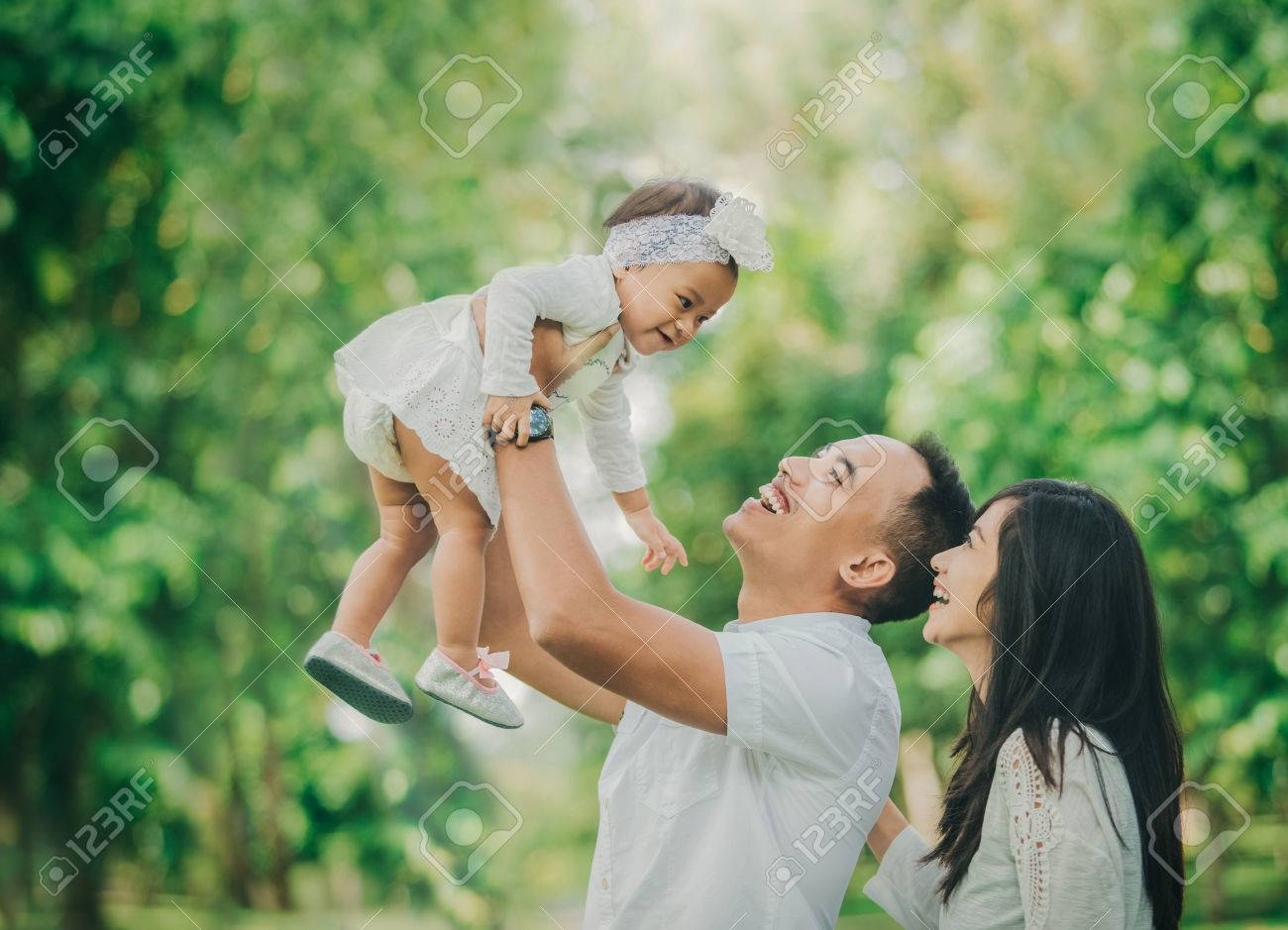 Portrait of beautiful family with cute baby in the park having fun together stock photo