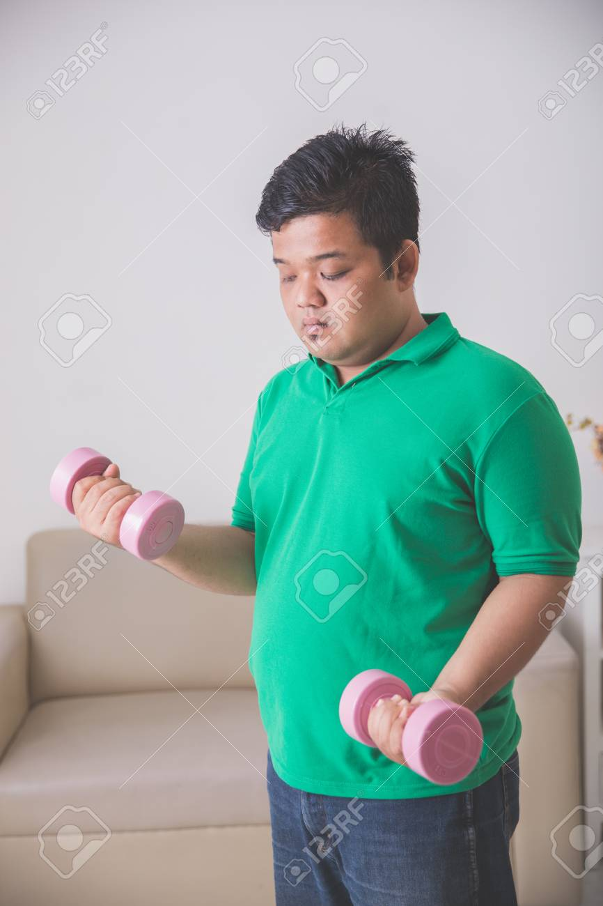 Portrait of overweight man doing exercise at home lifting up