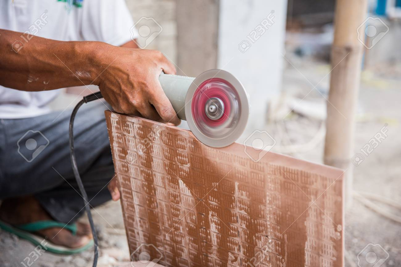 Worker cutting a tile using an angle grinder at construction stock worker cutting a tile using an angle grinder at construction site stock photo 82976132 dailygadgetfo Choice Image
