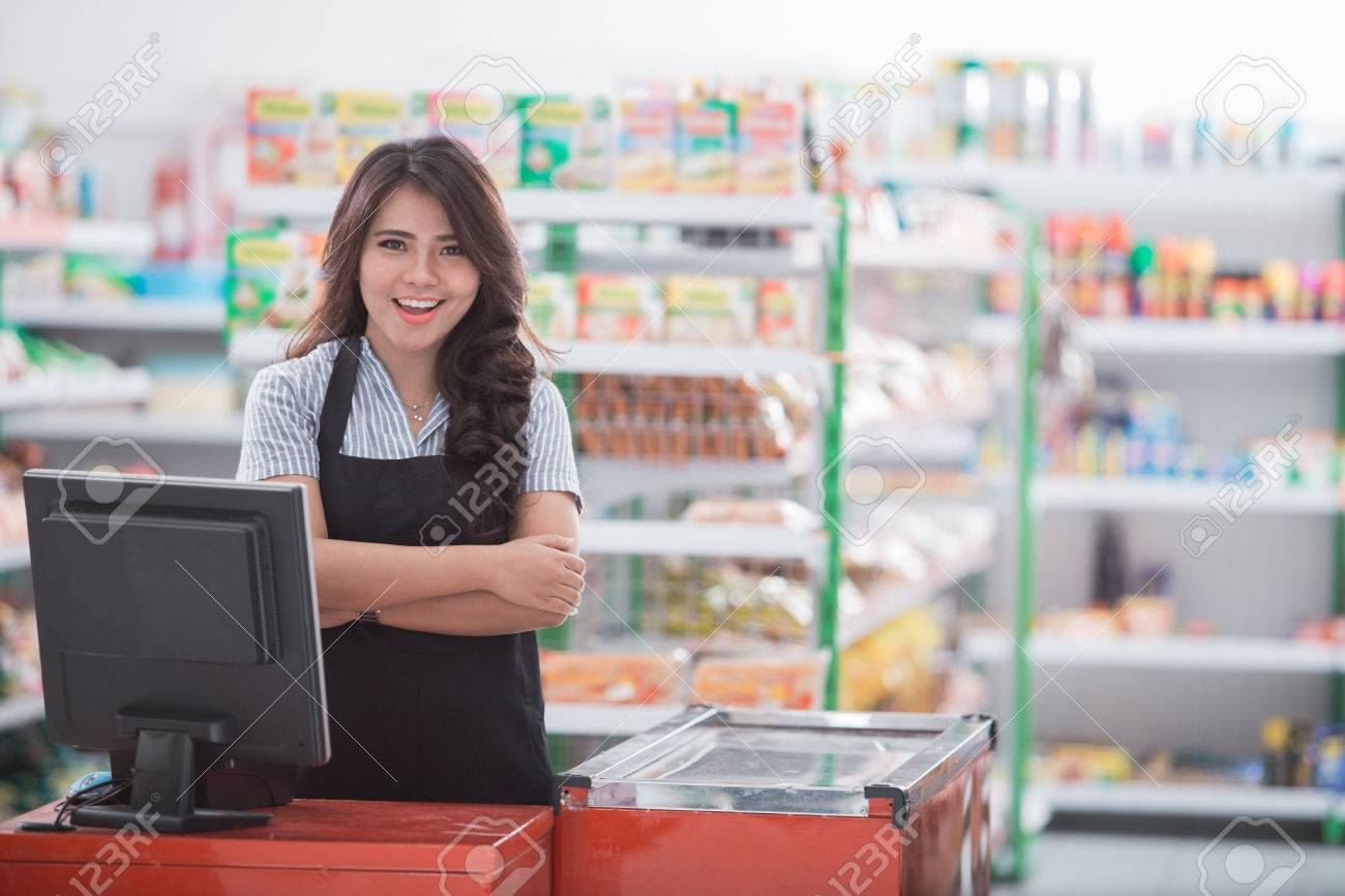portrait of young attractive woman at cash register in a store - 84486430