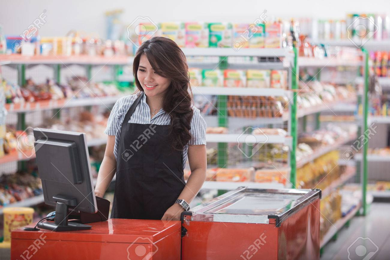 Portrait of smiling asian female staff standing at cash counter in supermarket - 84486432