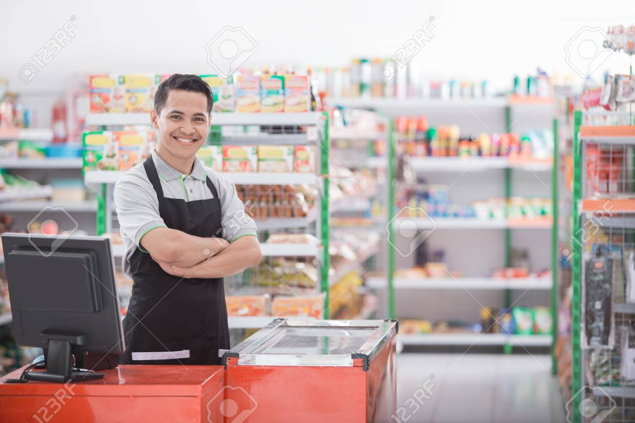 Portrait of a smiling shopkeeper in a grocery store - 89455314
