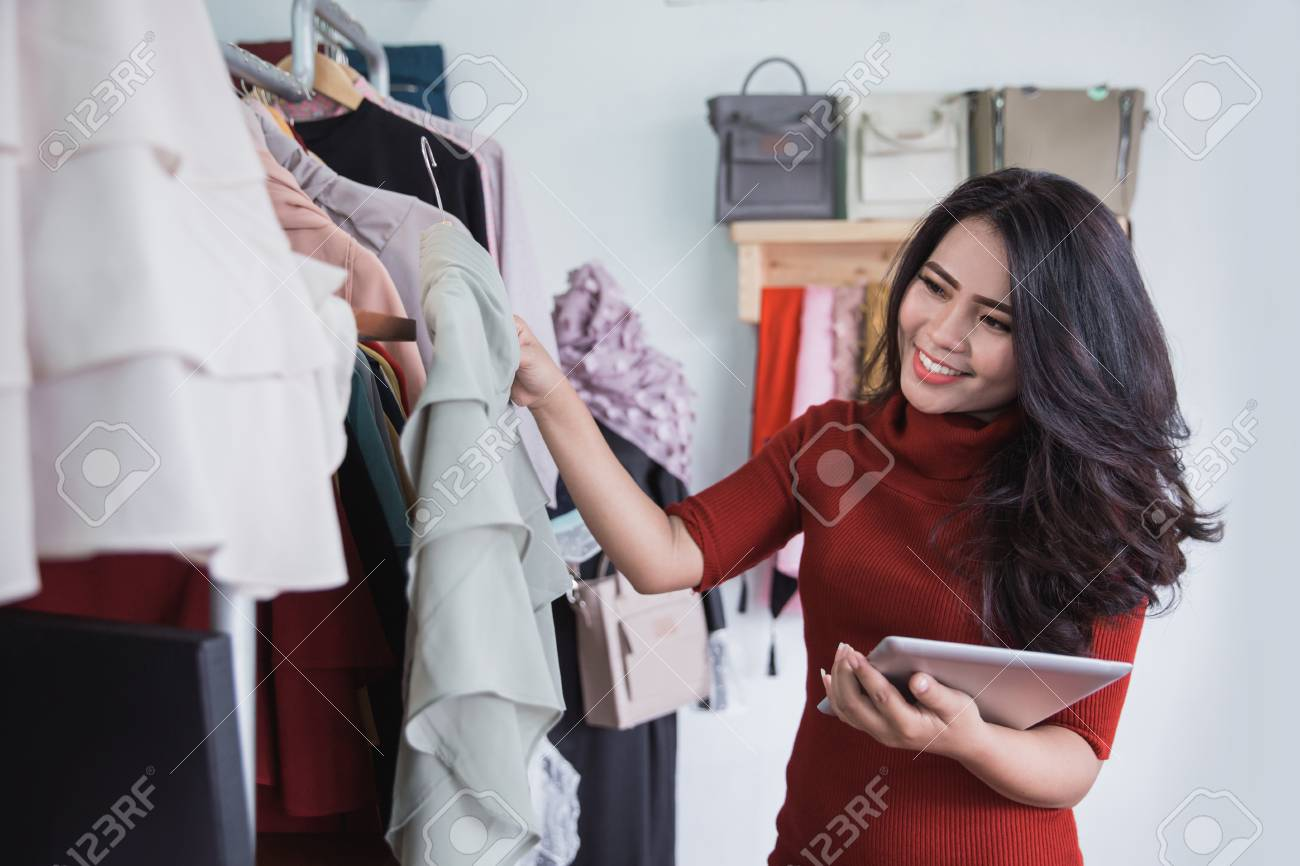 Beautiful woman using tablet while working in the store - 92565631