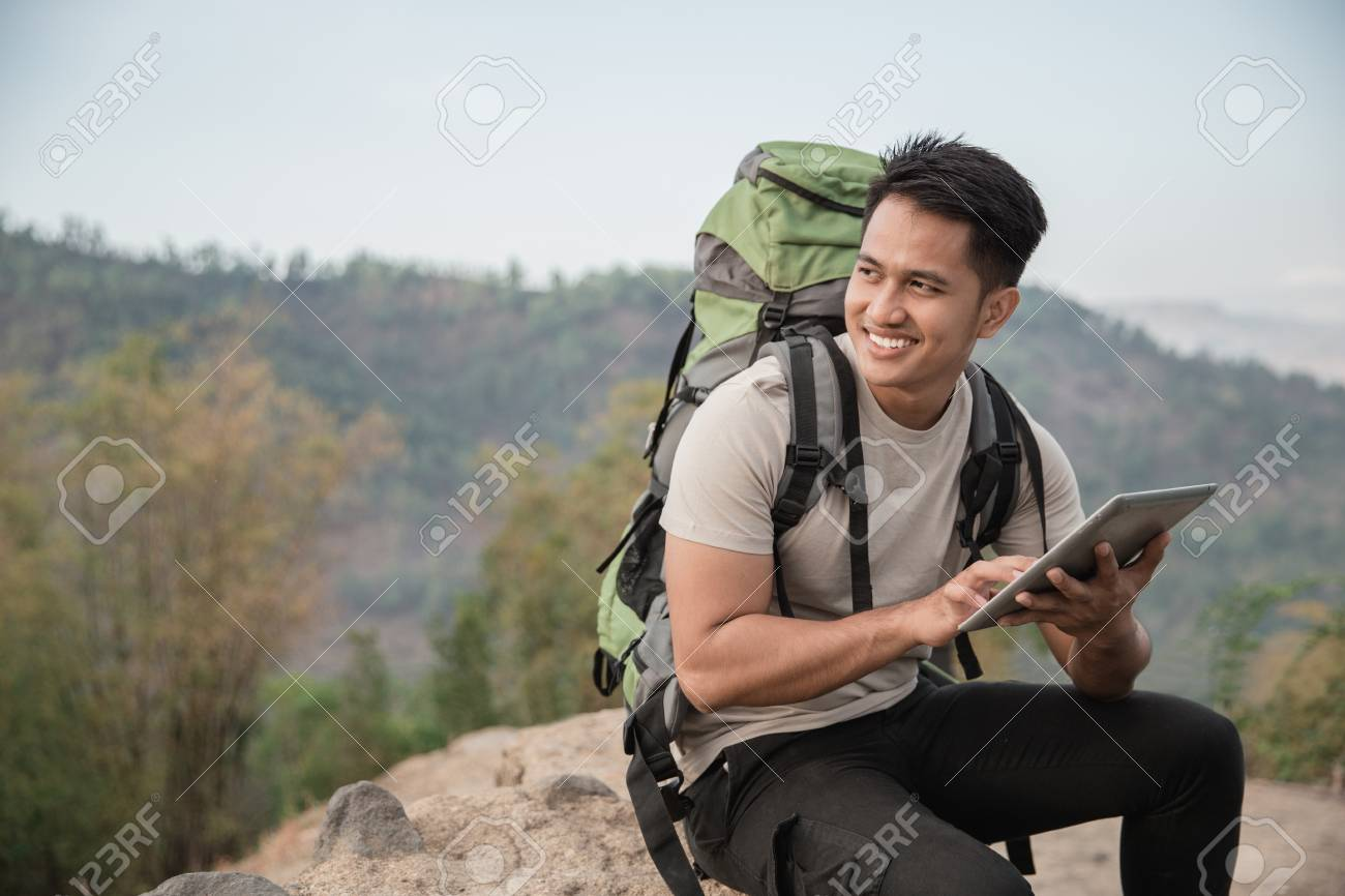 man hiker using tablet pc. while enjoying the view of the forest - 97271728