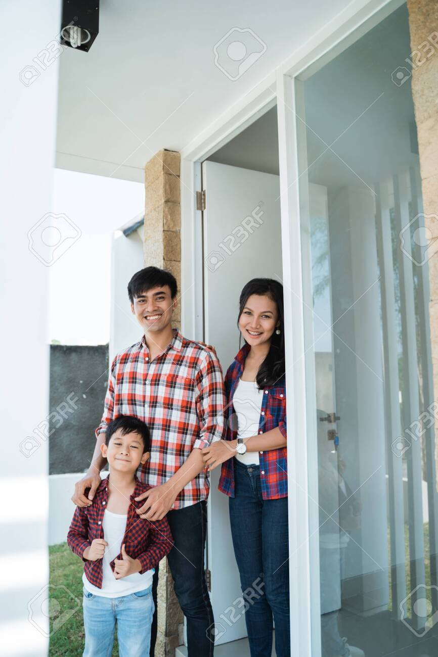 asian family in front of the door of their house - 121438033