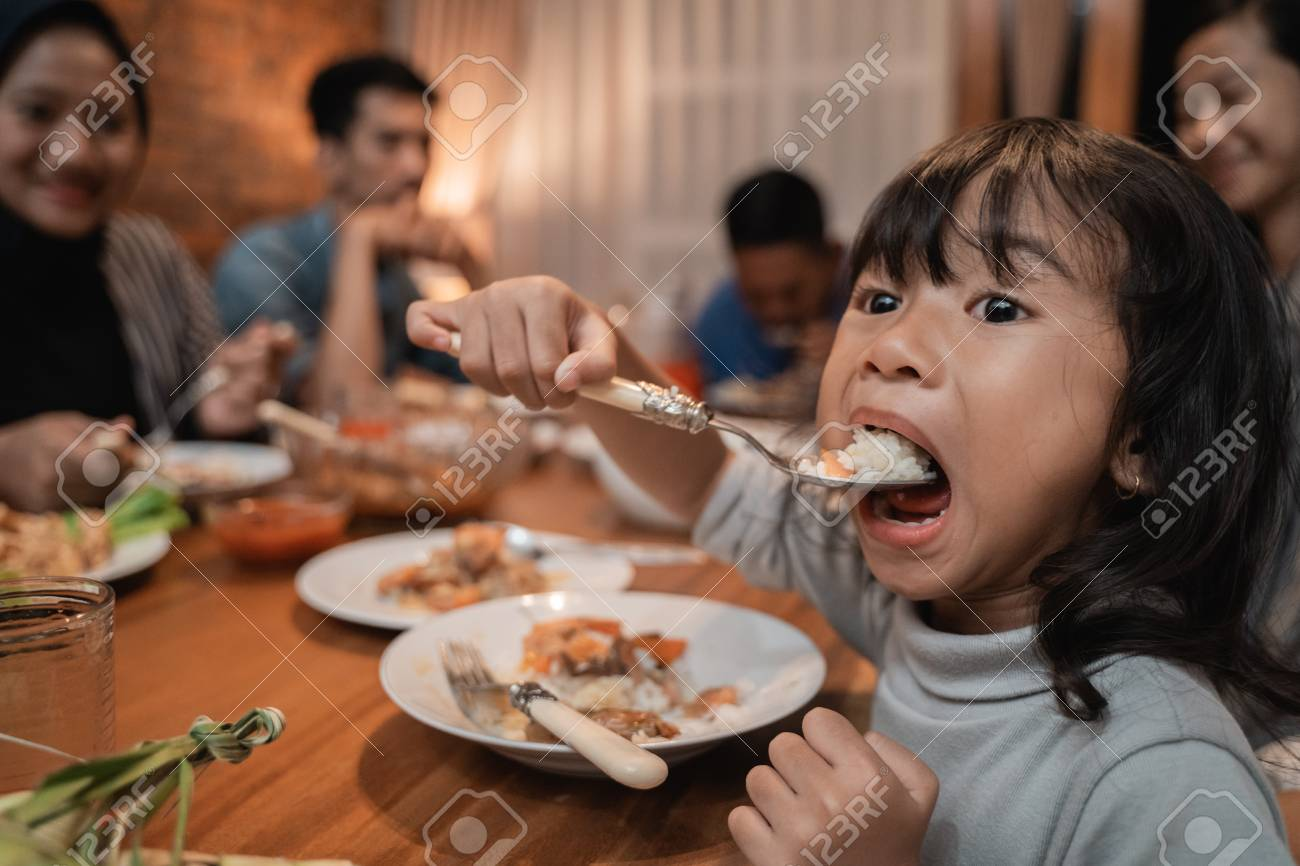 child daughter eating by herself during dinner - 121358065