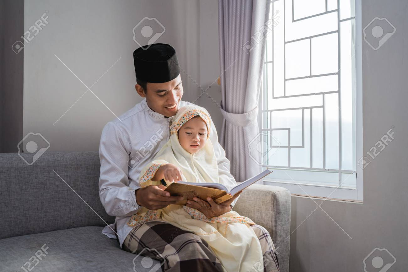 muslim father read quran with his daughter - 121558719