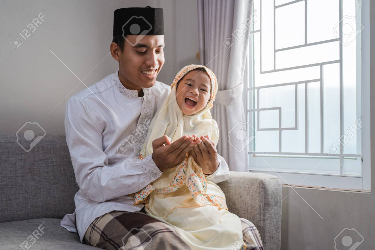 muslim father and kid praying together - 121558726