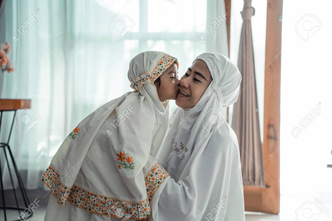 muslim young child kiss her mom after praying - 122175077