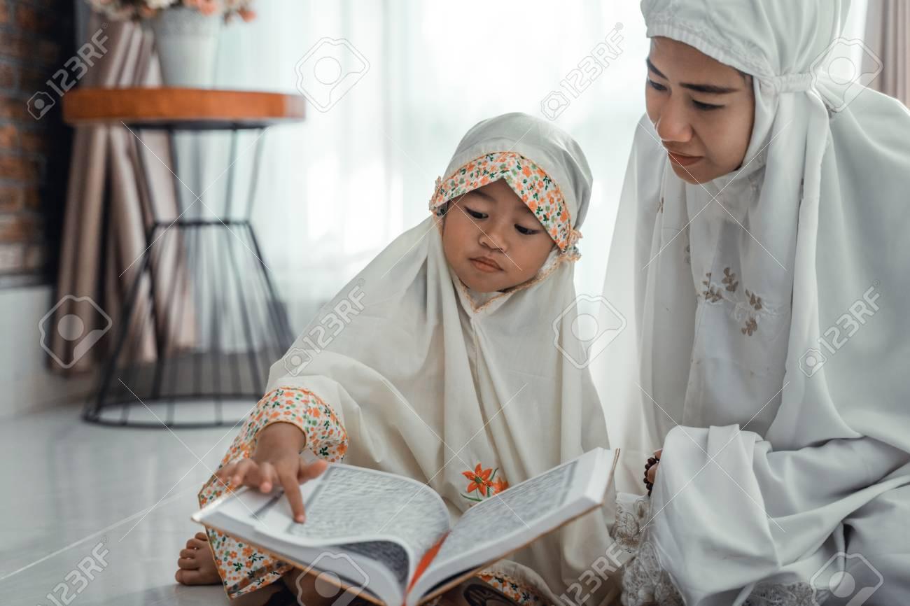 muslim parent and daughter reading quran - 122175188
