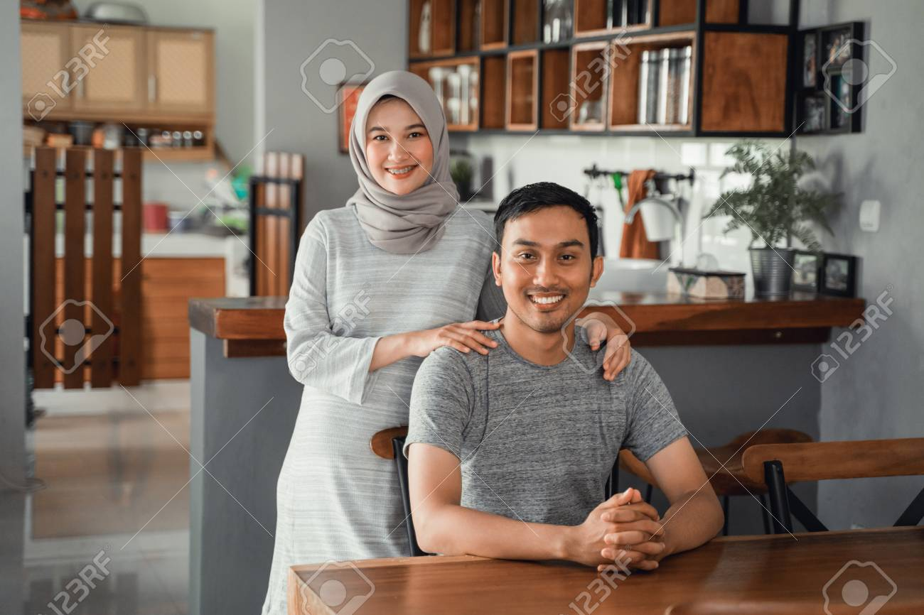 muslim couple sitting in dining room together - 122199482