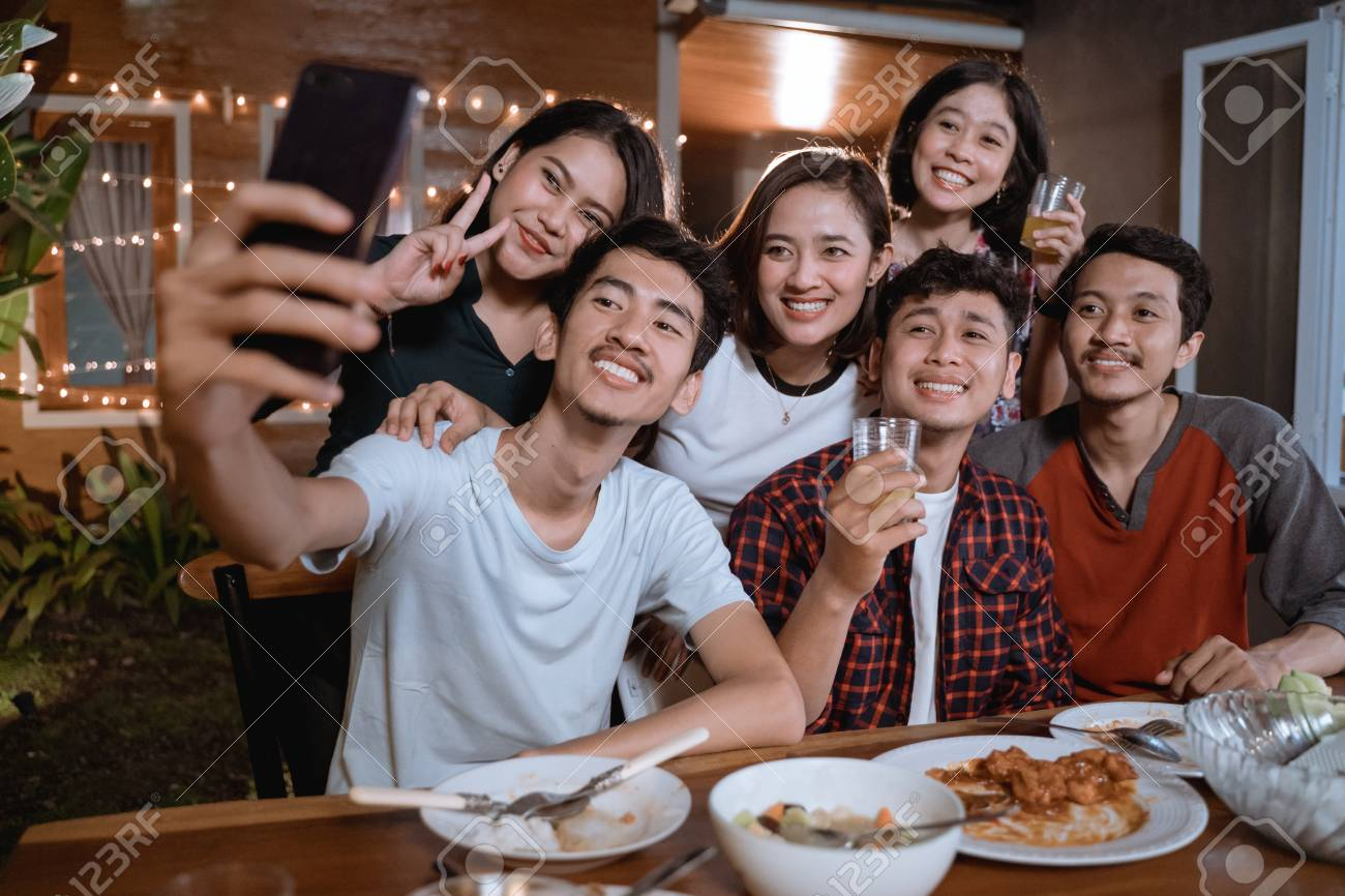 asian bestfriend group take selfie with smartphone while having garden party - 122811457