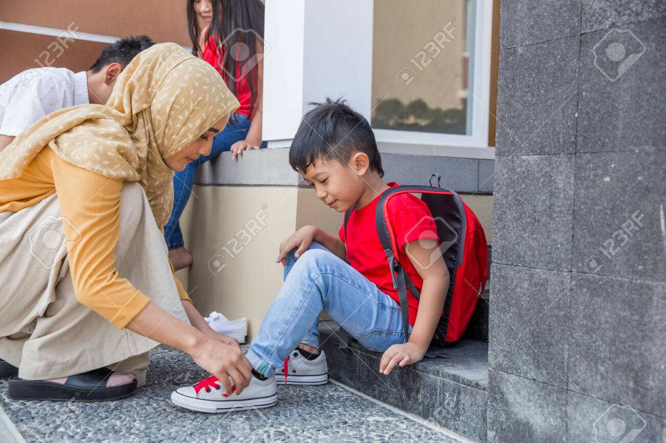 help her son to put on his shoes - 123430468