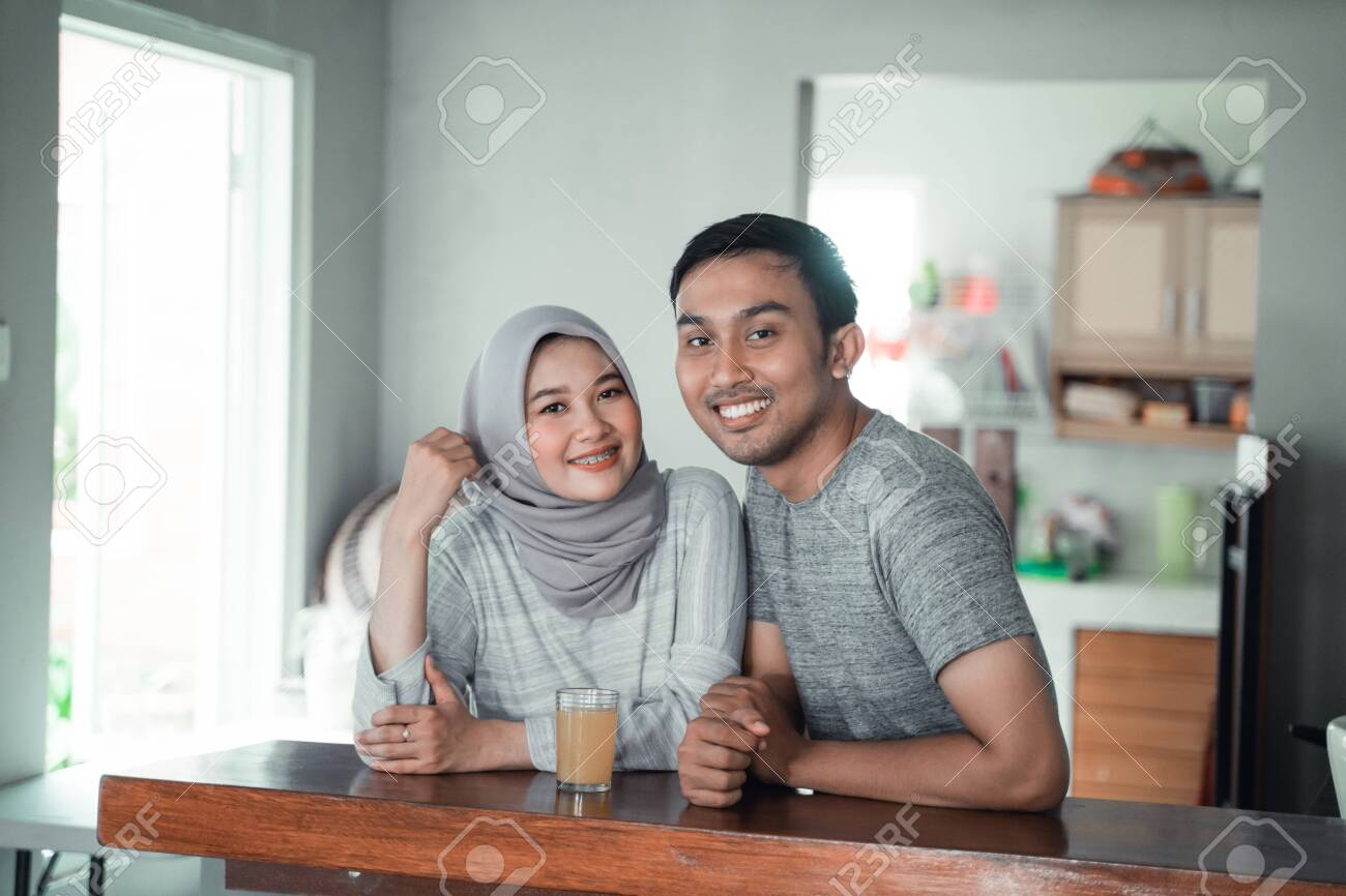 moslem couple relax sitting in the kitchen - 127048921