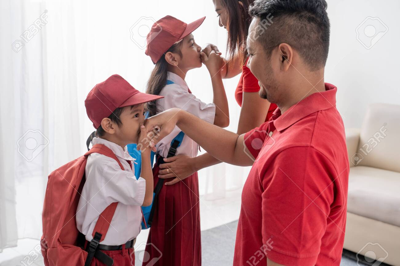 student kiss his parents hand before going to school - 127832822