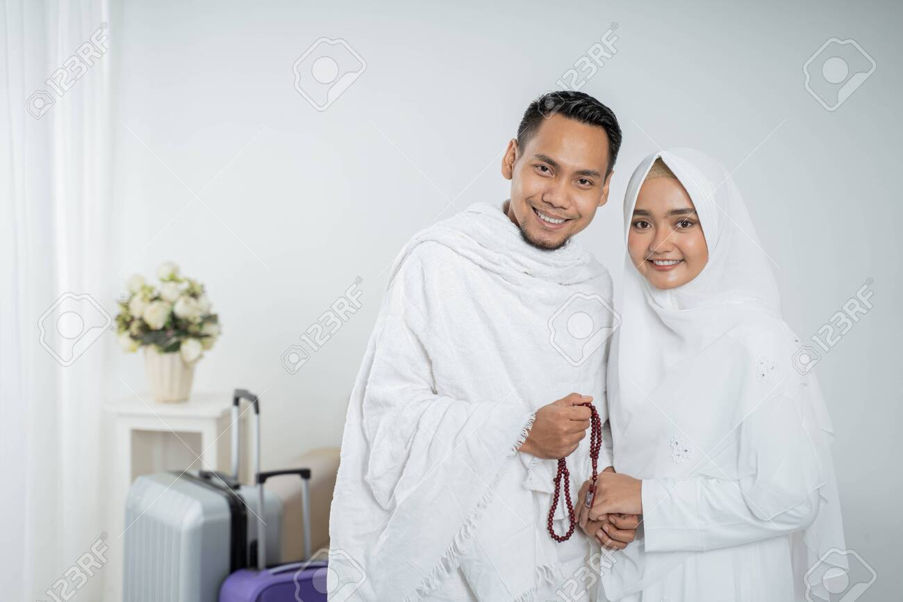 muslim pilgrims wife and husband in white traditional clothes - 128191523
